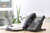 Executive VoIP phone on a beech desk